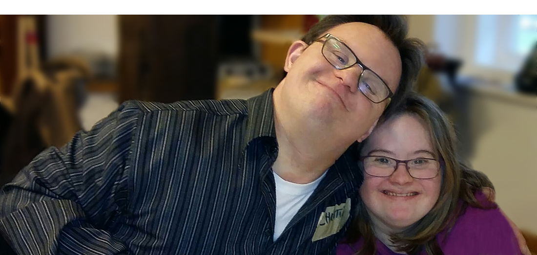 Eine junge Frau mit Down-Syndrom lehnt ihren Kopf an die Schulter eines jungen Mannes, der ebenfalls DS hat. Beide schauen glücklich und zufrieden.