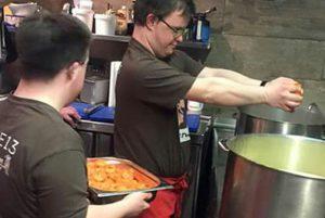 Zwei junge Männer in der Küche beim Kochen