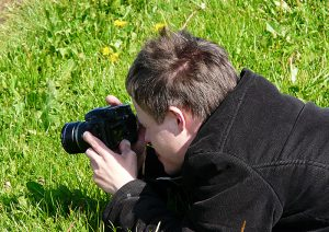Junger Mann mit Kamera macht eine Nahaufnahme auf einer Wiese